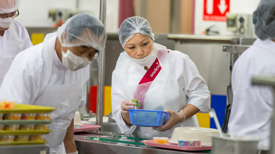 Employees wearing hairnets and masks while prepping food
