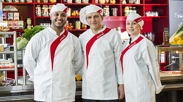 A group of Sodexo chefs posing for a picture in front of a counter